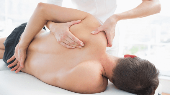 Man laying down receiving shoulder massage therapy